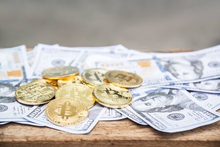Golden bitcoin coin on us dollars close up. Stock Photo