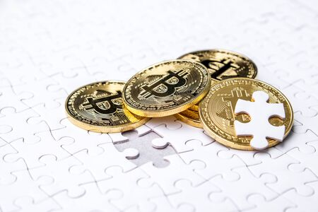 Gold bitcoin on white jigsaw or puzzle, cryptocurrency. Missing jigsaw puzzle pieces. Business solution concept, Key for success concept. Completing finance concept. Stock Photo - 98850049