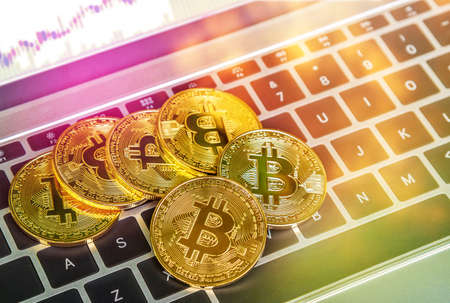 Golden bitcoins on laptop with charts,  Blockchain , cryptocurrencies investment security and strategy. Stock Photo