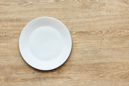 Top view of empty white food plate on a wood background. Template for your design.