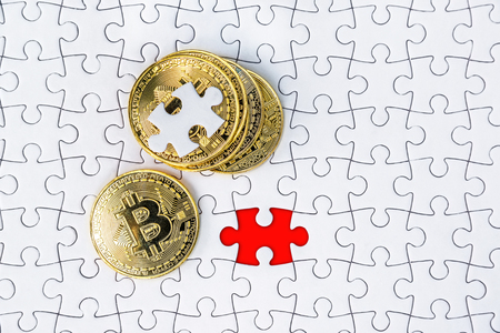 Gold bitcoin on white jigsaw or puzzle, cryptocurrency. Missing jigsaw puzzle pieces. Business solution concept, Key for success concept. Completing finance concept. Stock Photo