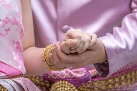 Close up of woman putting her hand on Thai man hand, engagement, Thai wedding loving and valentine concept.
