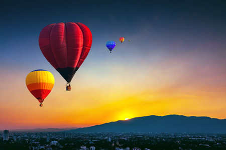 Aerial view colorful hot air balloons flying over Chiang Mai city in sunset ,Thailand.