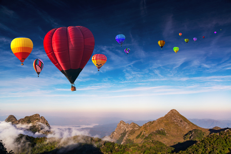 Aerial view colorful hot air balloons flying over with the mist at Doi Luang Chiang Dao with  morning mist in Chiang Mai, Thailand.  Stock Photo