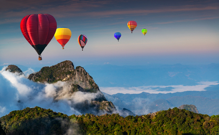 Aerial view colorful hot air balloons flying over with the mist at Doi Luang Chiang Dao with  morning mist in Chiang Mai, Thailand. Stock Photo - 100941245