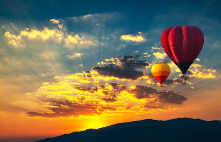 Aerial view colorful hot air balloons flying over sunset and golden clouds.