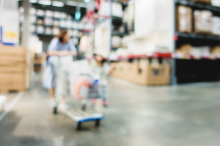 Blurry customers shopping in large warehouse with row of aisles. Industrial storehouse interior. Inventory, wholesale, logistic, export. With vintage effect filter. Stock Photo