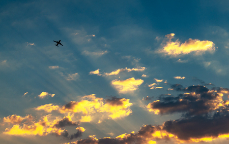 Sunset and golden clouds, light rays and other atmospheric effect with plane in sky