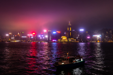 HONG KONG, CHINA - MAY 5, 2018: Tourist boats crosses Victoria harbour : Famous Junk crossing from Kowloon to the Hong Kong Island and skyscrapers of downtown at evening.