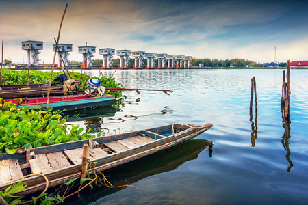 Local fishing boat of Thailand with Uthokwipat Prasit Watergate background for prevent sea water from flowing into the Pak phanang river, Nakhon Si Thammarat province, Thailand.