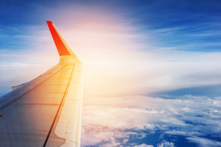 Wing of an airplane flying above the clouds. Stock Photo
