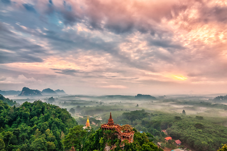 Landscape of beautiful sunrise with pagoda on peak mountain and tree with misty morning at Na Nai Luang temple , Surat Thani Province, Southern of Thailand
