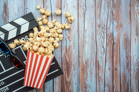 Cinema movie items, clapperboard, pop corn and 3d glasses on wooden background. Flat lay ,cinematography concept.