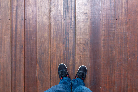 Selfie shot of feet man wearing sneakers standing on wooden floor, Top view with copy space