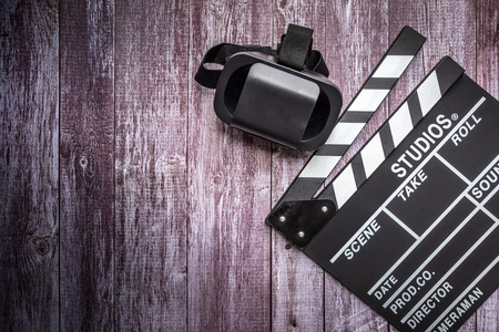 Clapperboard and VR Box  Virtual Reality glasses on wooden background.mock up, top view. Flat lay of cinema items. Stock Photo