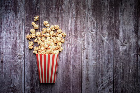 Flat lay of Paper cup with popcorn on wooden background, entertainment concept, mock up. top view. Stock Photo