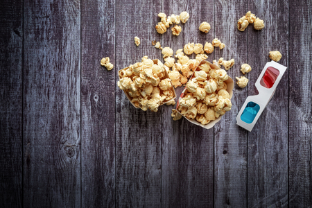 Cinema background, top view.  Popcorn and 3D glasses on wooden table. Movie accessories, cinematography concept, flat lay Stock Photo