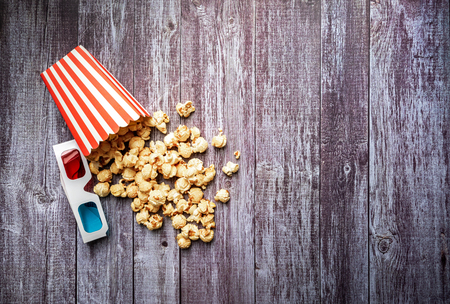 Pop corn and 3d glasses on wooden background. top view. Flat lay of cinema items. Stock Photo
