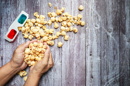 Man with popcorn in hand on wooden background. mock up, top view. Flat lay of cinema items.