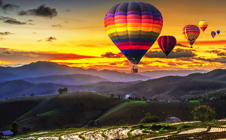 Colorful hot air balloons flying over Terraced Paddy Field in Mae-Jam Village , Chaing mai Province , Thailand. Stock Photo
