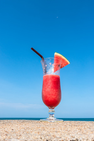 Fresh cold watermelon smoothies and beach on blue sea background Stock Photo