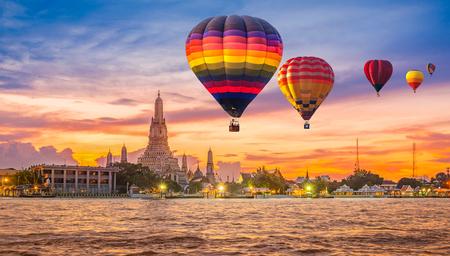 Colorful hot air balloons flying over Chao Phraya River near Wat Arun Temple at twilight in Bangkok, Thailand