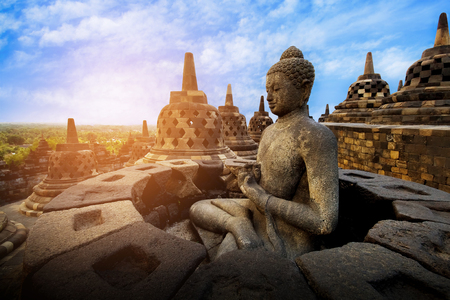 View of meditating Buddha statue and stone stupas against sunrise. Great religious architecture. Magelang, Central Java, Indonesia