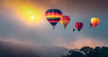 Montgolfières volant au-dessus de la haute montagne au lever du soleil à Dot Inthanon à Chiang Mai, Thaïlande. Image filtrée: effet vintage traité en croix