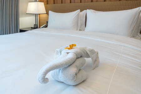 Towels Animal Designs on bed in stylish bedroom interior.