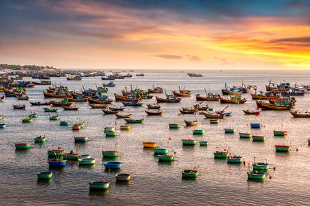 Traditional Vietnamese boat in the basket shaped on fishing port at Fishing village in sunset sky , Binh Thuan, Vietnam. Landscape. Popular landmark, famous destination of Vietnam