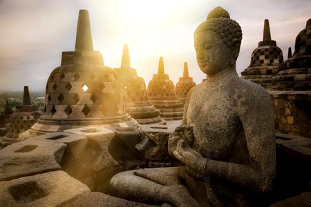 Blick auf meditierende Buddha-Statue und steinerne Stupas gegen Sonnenaufgang. Große religiöse Architektur. Magelang, Zentraljava, Indonesien