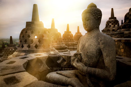 View of meditating Buddha statue and stone stupas against sunrise. Great religious architecture. Magelang, Central Java, Indonesia Фото со стока - 116349509