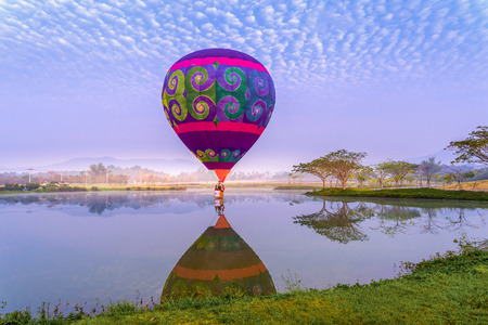 CHIANG RAI, THAILNAD - 16 FUBRUARY 2019 : Colorful hot air balloons floating above the lake with blue sky in Singha Park ,Chiang Rai, Thailand Editorial