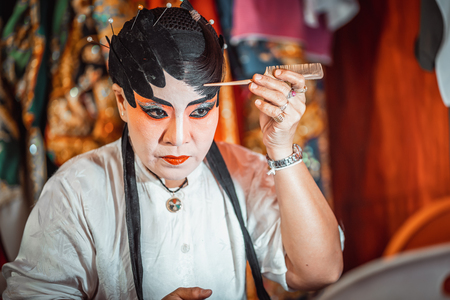 CHIANG MAI, THAILAND - FEBRUARY 24, 2019: Close-up of a chinese opera actress is doing the make up, cantonese opera dummy.