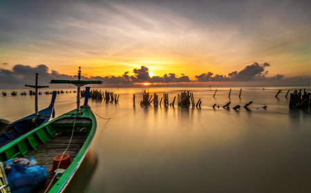 Front view of bow wooden fishing boat and sea background in sunrise with copy space, Long exposure Imagens