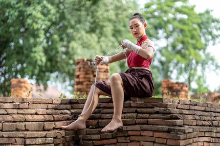 Close-up of a young woman Muay Thai fighter preparing and wrapping her hand with traditional hemp ropes before the fight or training. Imagens