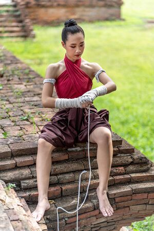 Close-up of a young woman Muay Thai fighter preparing and wrapping her hand with traditional hemp ropes before the fight or training. Stock Photo