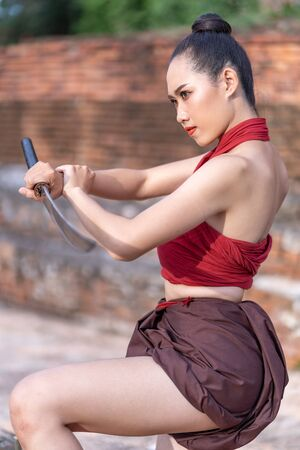 Asian woman warrior in Ayutthaya costume holding sword fight. Warrior woman of soldier of Bang Rachan in Thailand. Imagens