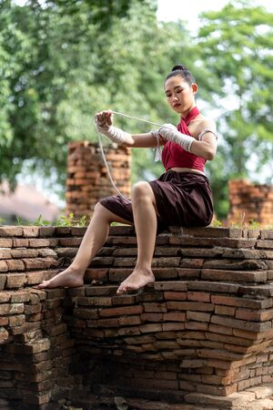 Close-up of a young woman Muay Thai fighter preparing and wrapping her hand with traditional hemp ropes before the fight or training. Imagens - 131127904