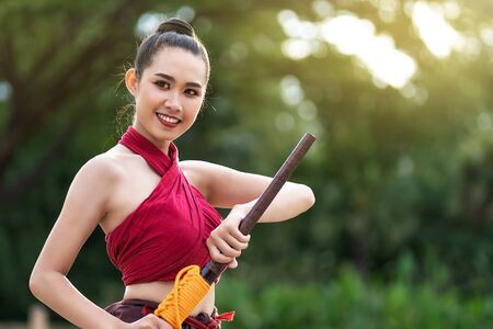 Asian woman warrior in Ayutthaya costume holding sword fight. Warrior woman of soldier of Bang Rachan in Thailand. Imagens - 131127980