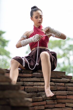 Close-up of a young woman Muay Thai fighter preparing and wrapping her hand with traditional hemp ropes before the fight or training. Imagens - 131127981