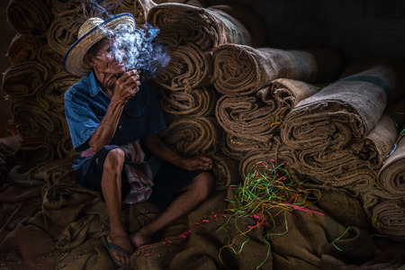 Old man smoking cigarette and the smoke released from the mouth