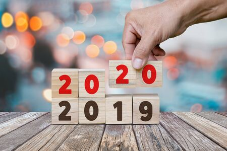 New Year concept from 2019 to 2020, Hand holds cube and changes wooden cubes to Year 2020.