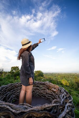 Tourist woman taking travel picture with smartphone at mountain peak cliff during summer holidays. Banco de Imagens