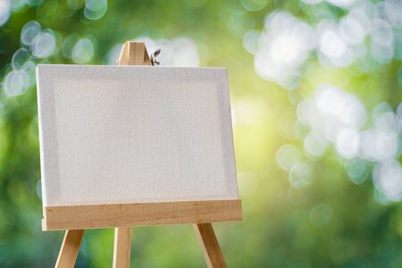 White empty artistic canvas on an easel and green bokeh background Фото со стока