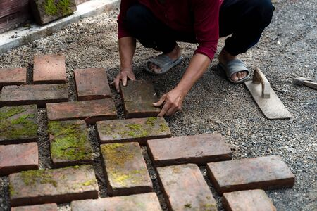 Worker laying red brick on floor. Road Paving, construction.