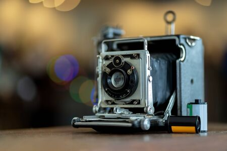 Retro film photo camera isolated on blurred background at light bokeh.