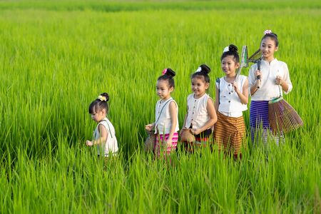 Asian children in rice fields with countryside background