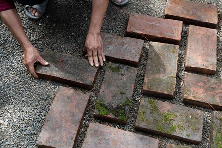 Worker laying red brick on floor. Road Paving, construction. Stockfoto - 129737574