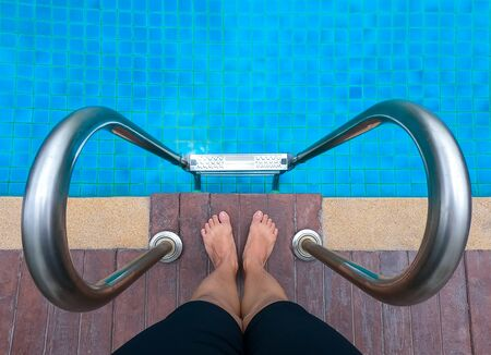 Feet standing on stone border in front of stairs pool , summer vacation concept